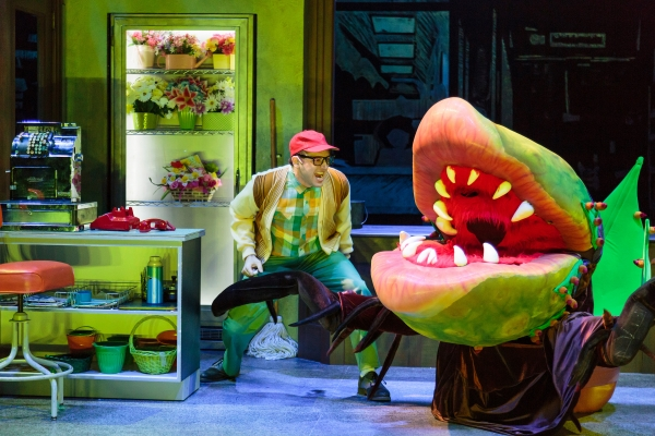 Seymour (Joshua Carter) and the Audrey II (puppeteer: Eric Esteb, voice: Ekello Harrid Jr.) in Little Shop of Horrors, a co-production of ACT and The 5th Avenue Theatre.   Credit: Tracy Martin